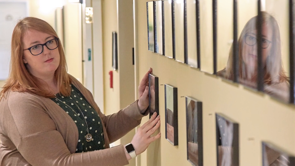 Programming Director Jill Flores-Cordon, Benchmark Senior Living at Waltham Crossings, puts the final touches on the gallery.