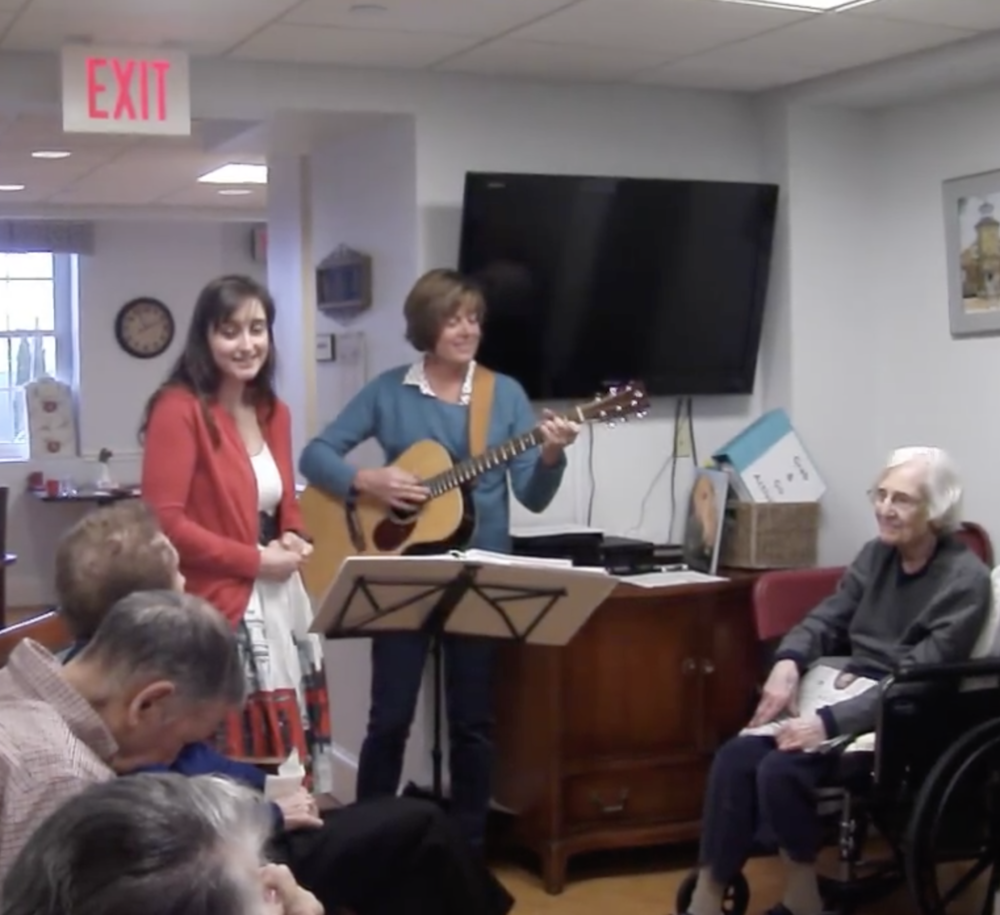 """Benchmark Connections Coordinator  Alyson Fowler , accompanied by Dot, sings """"What a Wonderful World"""" to residents of Academy Point."""