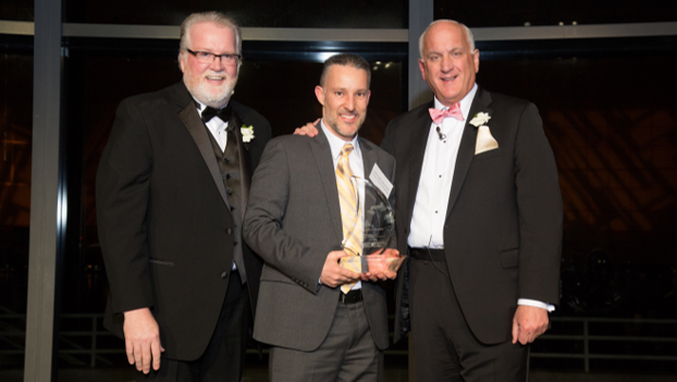 Coachman Square at Woodbridge Dining Services Director  Christopher Raymond , center, accepts the Navigation Award for his community from Bob Moran and Tom.