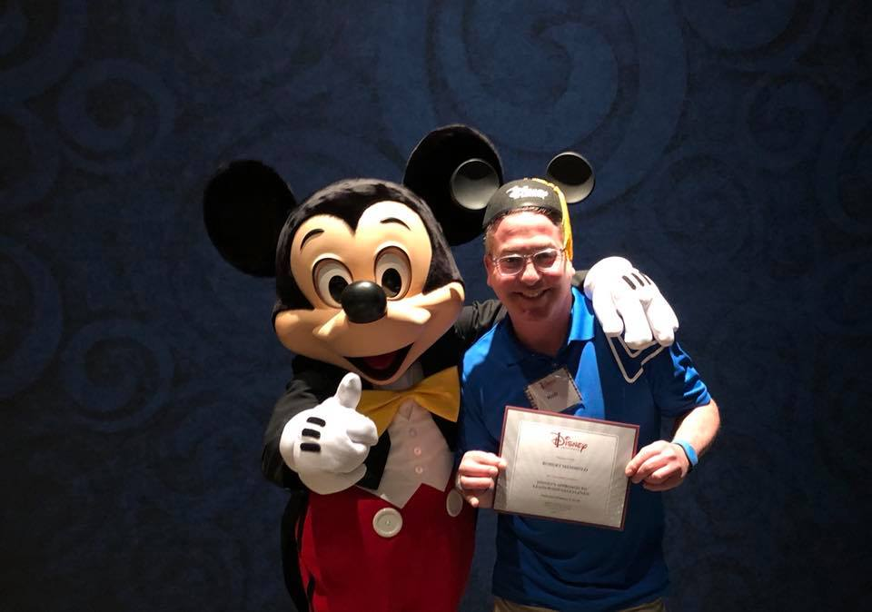 Rob accepts his Disney Institute diploma from … do we really have to identify this beloved character?