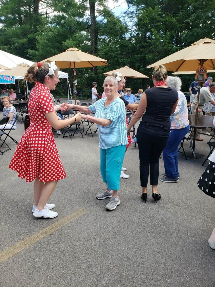 Hannah John   , server, dances with resident Jean Robitalle.
