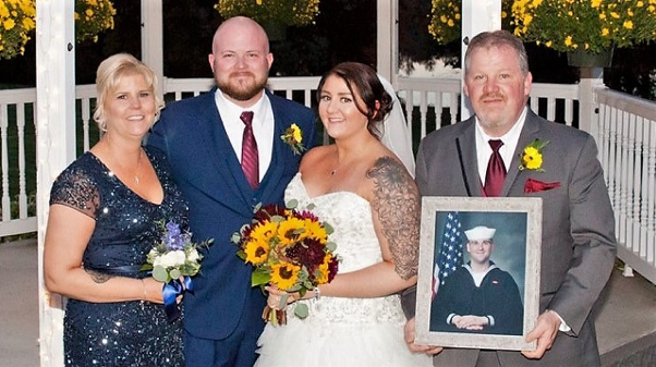 At her summer 2018 wedding. Allison with her husband, Donny Welch, and her proud parents, Rene Hourihan and Regional Director of Dining Services Jim Hourihan, holding a photo of his son, Petty Officer 3rd class Mark Hourihan, who is serving in the U.S. Navy in Japan and studying cybersecurity.