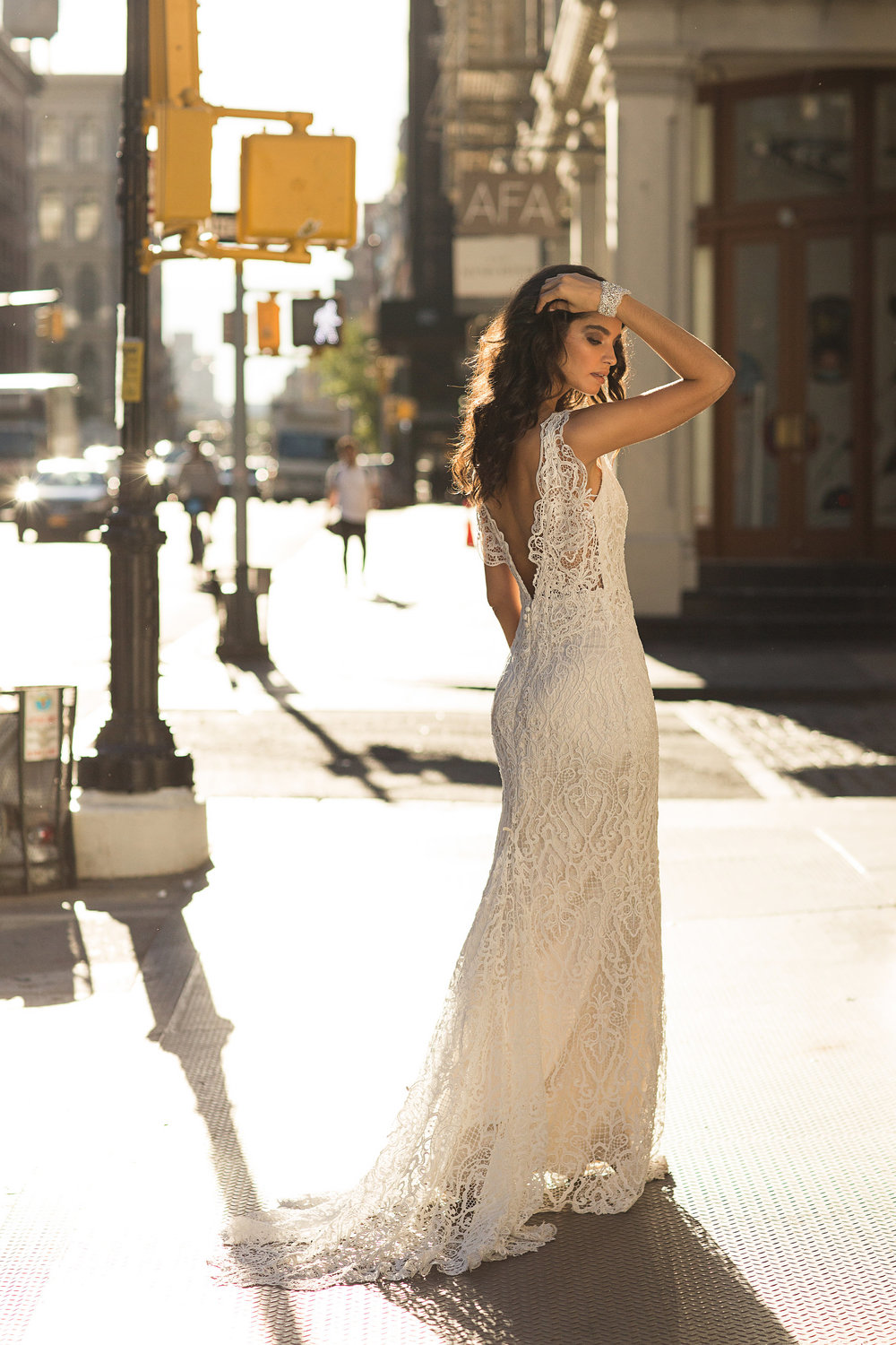 Kira Dress - A modern, ivory guipure lace in a classic, fitted bridal silhouette. Additional lace motifs on the shoulders create a unique and unexpected detail, while a matching motif at the tip of the in-built lace train ensures a grand exit.Styled with the Pearl Cuff.