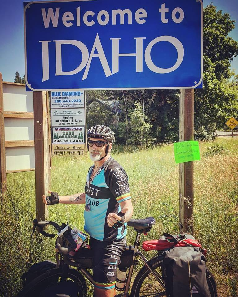 "Mike Robertson standing under a sign that reads, ""Welcome to Idaho"""