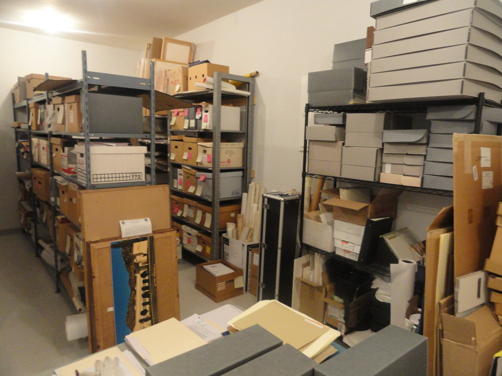 This is the backlog. These items have been waiting to be added to the collection for a long time - sometimes several decades. Lots of them are actually artifacts and were brought to the Museum instead. Note the sticky note labels, acidic boxes housing items, and items overhanging the shelves.
