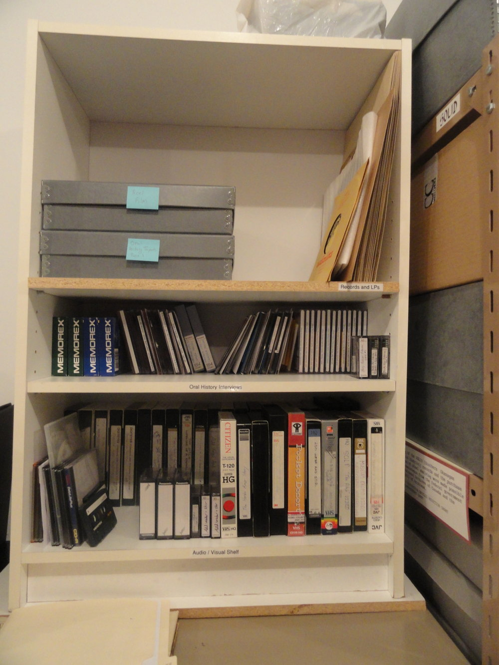 Our audio-visual shelf was also a wood composite, with items stacked several items deep on the shelves, making access difficult. Most items were also exposed to dust and UV radiation.