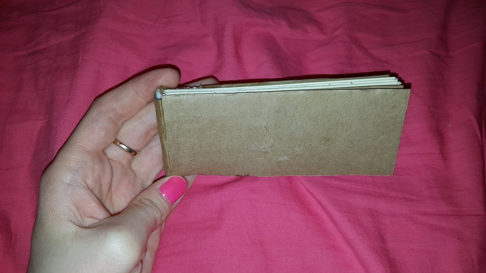 Click the image to see more detailed photos!  I made this little book from scratch as a present. I started by binding the card-stock pages in small groups. I then laced ribbon through the binding, and glued the loose ends of ribbon to the outermost card-stock pages. I added some cheese cloth on the spine to give it some structure, then I glued the spine piece onto the outer pieces of card-stock. I used a cover piece to strengthen the bond between the spine and the outer card-stock.