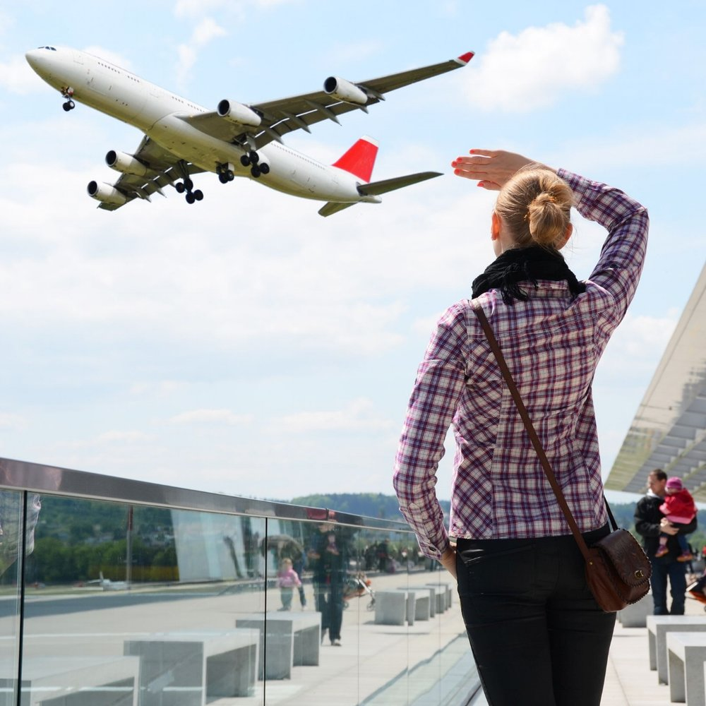 blonde haired female tourist watching aircraft flying overhead