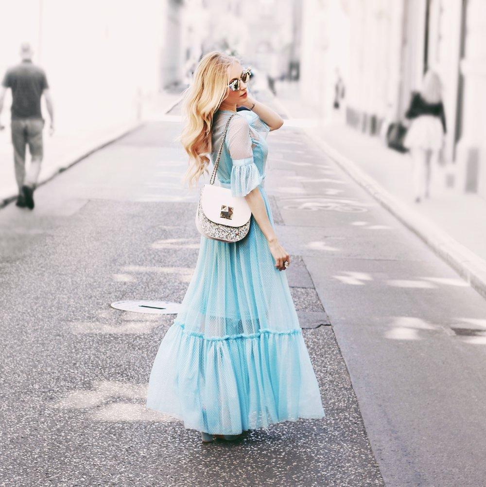 """A szívem mélyén mindig is különös vonzalmat éreztem a Disney-mesékre emlékeztető ruhák iránt... Az egyik kedvencem a Hamupipőke volt, így amikor megrendeltem ezt a csodaszép kék ruhát, egyből gyermekkorom szeretett meséje ugrott be róla. Kicsit átfogalmaztam, és beillesztettem a budapesti urbánus környezetbe, így egy egészen furcsa - modern ám mégis mesebeli hangulatot létrehozva. A különleges kristályokkal kirakott Cango & Rinaldi napszemüveg pedig már csak hab a tortán, a hozzá tartozó glitteres táskáról és kristály gyűrűről már nem is beszélve... Imádtam ezt a fotózást, de főleg azt, amikor egy mellettünk elsétáló kislány ezt kérdezte az anyukájától: ,,Anya, anya, ez egy igazi hercegnő?!"""""""