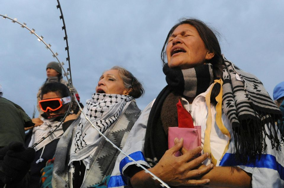 971245-women-hold-a-prayer-ceremony-on-backwater-bridge-during-a-protest-against-plans-to-pass-the-dakota-a.jpg