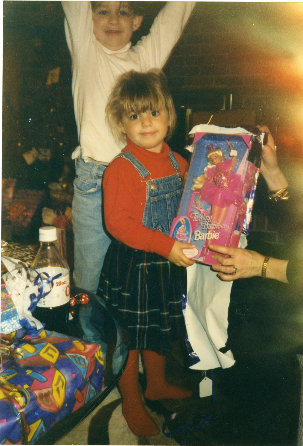The author revels in her Hanukkah gift during a Hanukkah party. (Emily Levinson and her brother, Chase - 1990's)
