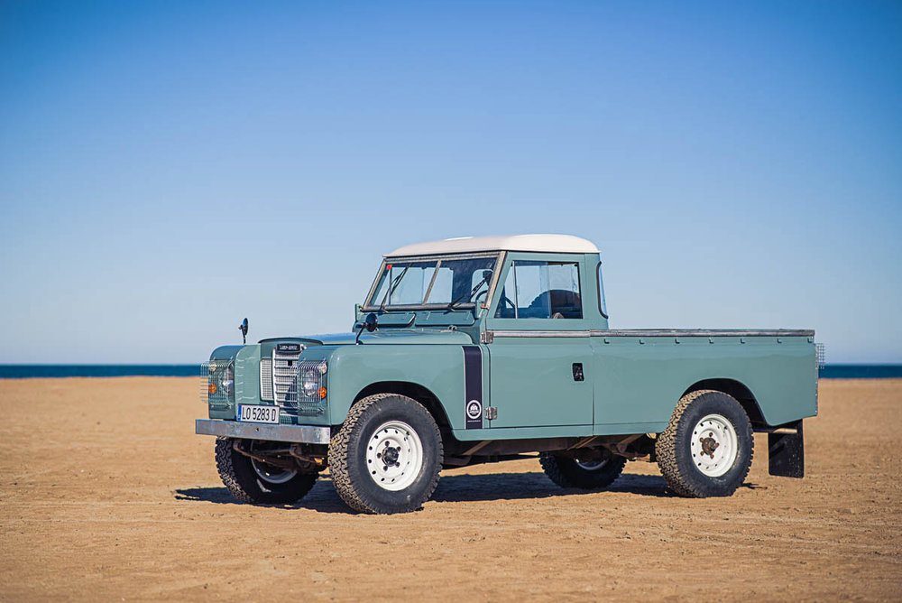 A custom Series III Land Rover pickup in early RAF Blue/Gray with White roof and Wolf wheels, and gray quilted seats in antique leather.  This vehicle was originally Sand colored.