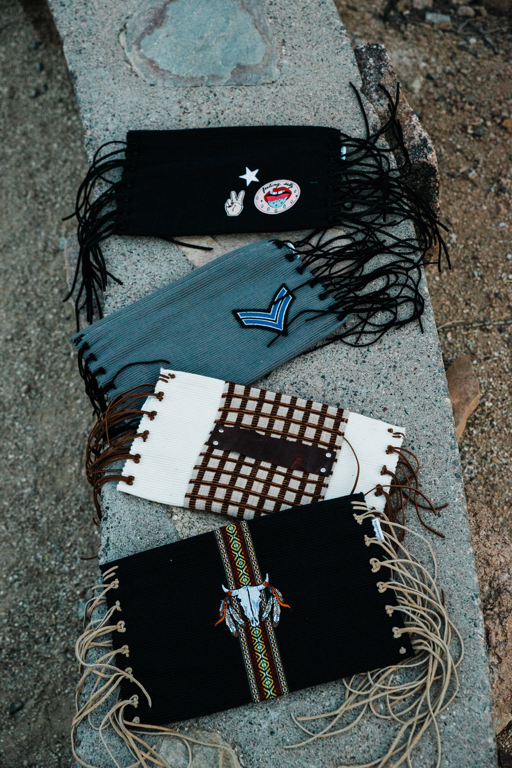 Four gorgeous fringe bags from Hippie Momma Bags laying in the Arizona desert