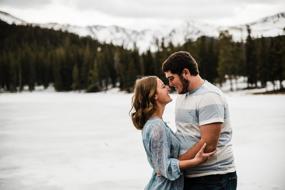 Echo Lake, frozen beautiful snow covered lake and mountains.  Mount Evans the 14er in the back ground.  Sarah and Randy In love at their engagement session.