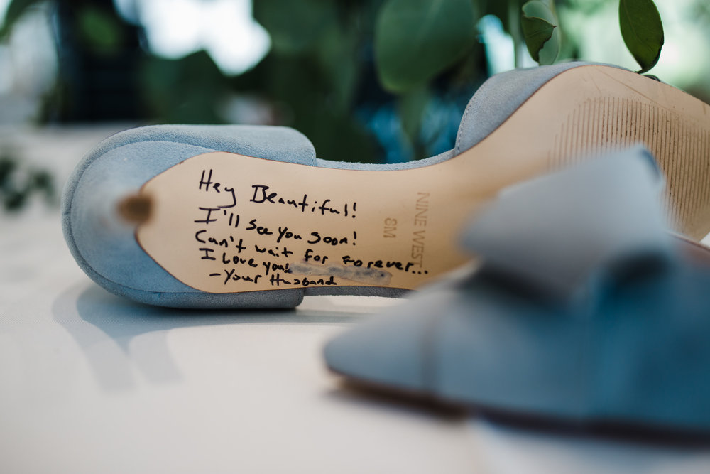 Colorado mountain wedding photographer at Brookeside Gardens of bottom of brides shoe with a message from groom