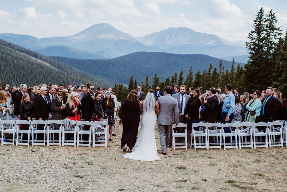 Bride and parents walking down the aisle at Keystone, Colorado mountain wedding