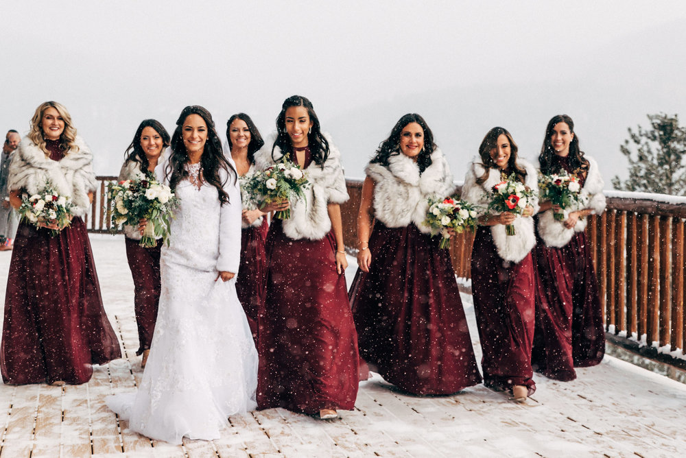 Bridesmaids doing the catwalk on the snowy mountain deck. Colorado wedding photographer.