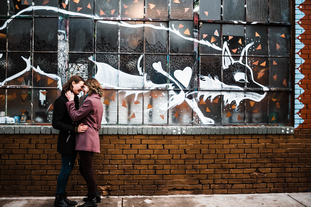 Beautiful trans couple in love in front of a downtown Denver Colorado RiNo art mural, RiNo Arts District, RiNo engagement session, LGBT wedding photographers, LGBT friendly wedding photographers, LGBT engagement photographers, Denver wedding photographers, Denver Engagement photographers