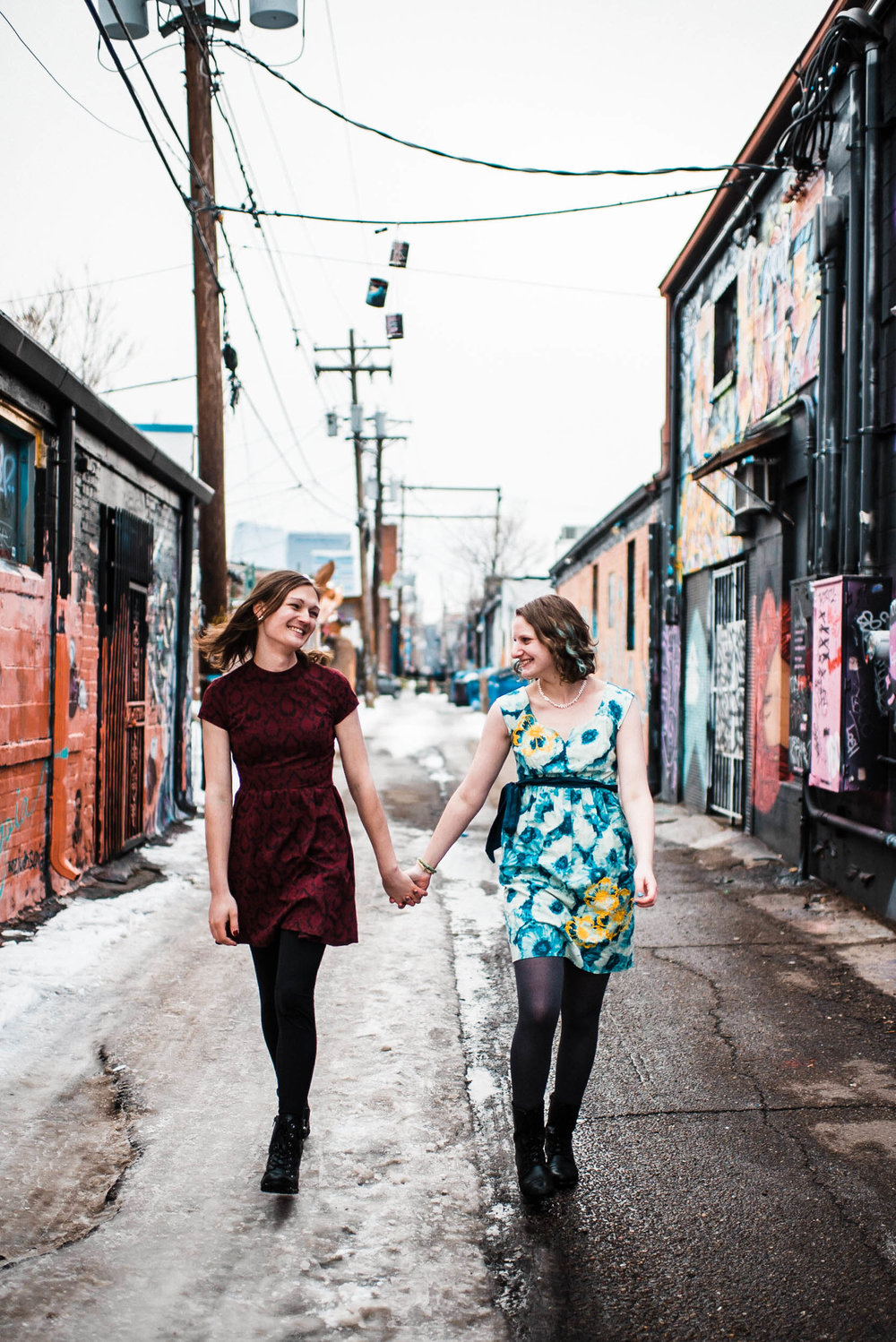 Beautiful lesbian trans couple walking down the alley in Denver Colorado RiNo art mural, RiNo Arts District, RiNo engagement session, LGBT wedding photographers, LGBT friendly wedding photographers, LGBT engagement photographers, Denver wedding photographers, Denver Engagement photographers