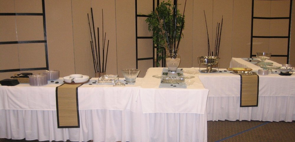 This was a $150-$200 reception for a couple who spent a lot of time in Japan. Duct tape played a large part in the design. We used it on the room dividers to create a shoji screen effect as well as on the table runners as trim. Notice the rocks on the table and painted bamboo in glass jars filled with sand.