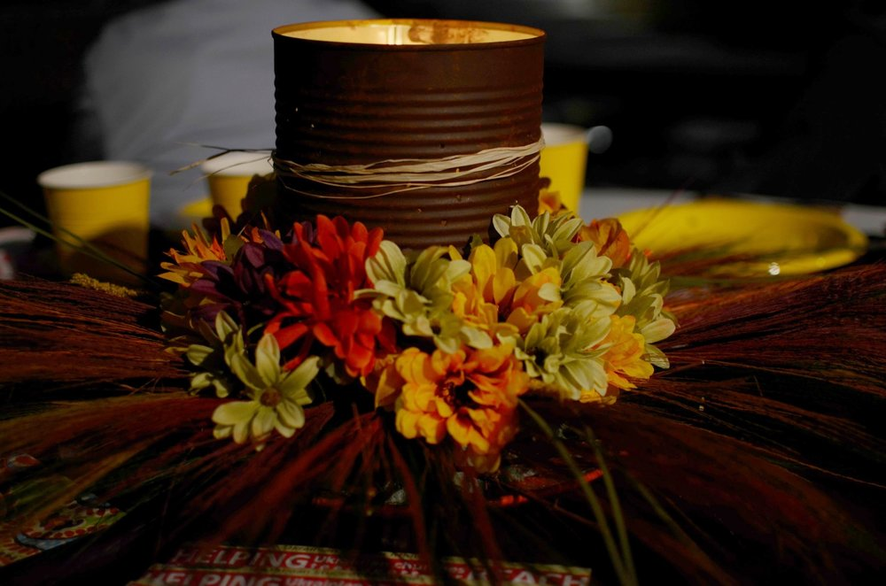This centerpiece consists of a #10 tin can given a rust patina, surrounded by artificial flowers and grasses.