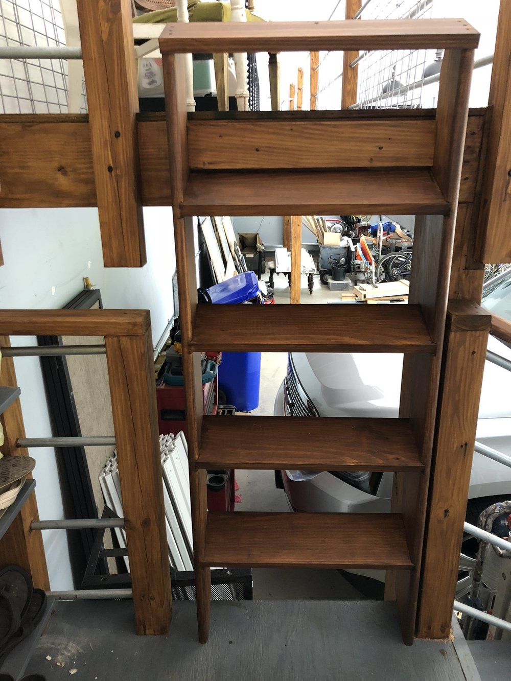 When in storage mode, the ladder is part of the railing for the landing but then pulls out to access the loft.