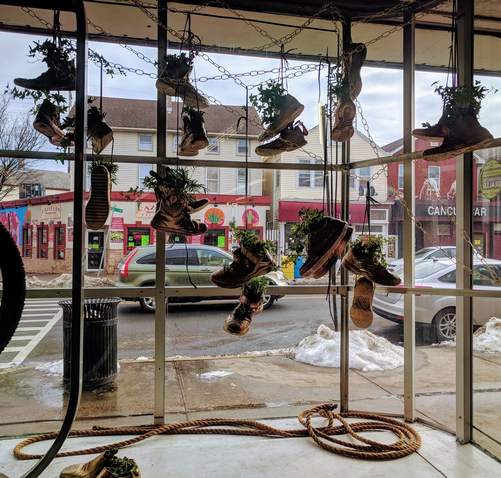 LTNLTL - Listen to your neighbor, listen to the land (LTNLTL) consists of old sneakers up-cycled into functioning hanging planters and hung like shoes over telephone wire. This ubiquitous meme speaks to the enigmatic nature of human activity within a fickle and continuously churning city.  It pays homage to public spaces rife with multiple meanings, conflicting resonances, and opposing value judgments.  It offers the viewer hope via the simple beauty of living foliage. Nature is our neighbor and she speaks her systems to us whether we listen or not, to our benefit or not.  How we treat each other echos inside of how we treat the land that surrounds us.