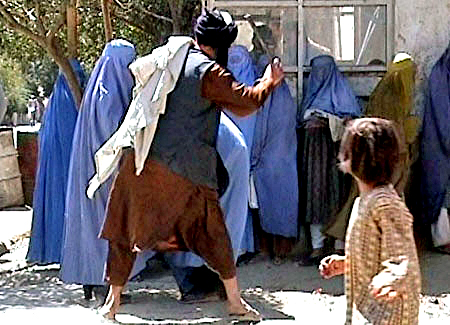 Taliban religious police beating a woman because she dared to remove her burqa in public