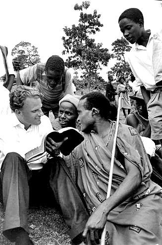 During his 1960 African crusade, Billy Graham explains the Bible to a group of Waarusha warriors living in a village at the base of Mount Meru, not far from Kilimanjaro, in Tanganyika (now Tanzania).