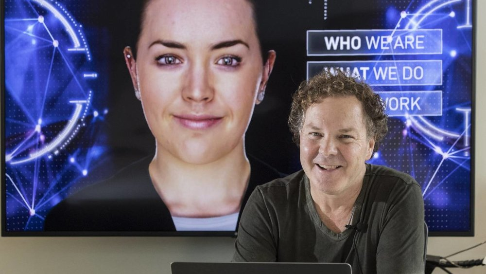 """Greg Cross, Soul Machines' chief business officer, believes by adding human-like faces to AI systems, such as """"Rachel"""", behind him, consumers will more readily interact with them"""