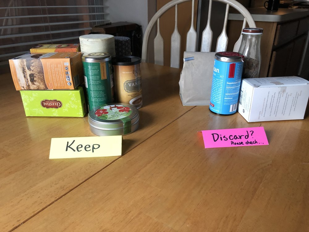 The easiest way I have found to have my family weigh in on what stays and what goes: take a small communally-owned category of stuff out of its storage, leave it on the kitchen table, and let family members move items into the discard or the keep pile.