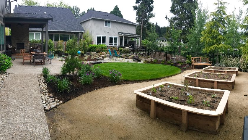 Backyard landscaping with raised garden beds and patio