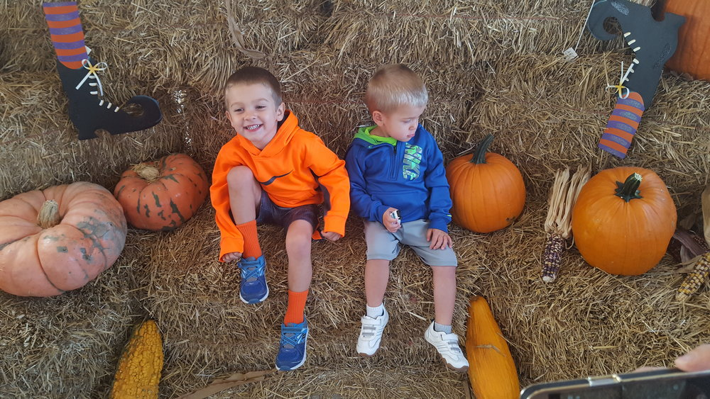 Landon doesn't like sitting on the hay.  Jackson was so excited to sit by the pumpkins!