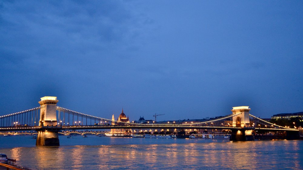 Budapest Széchenyi Chain Bridge at night with Budapest Parliament in the distance.
