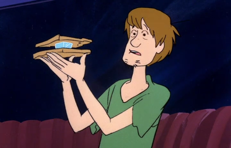 "Shaggy holds aloft what is colloquially referred to as a ""Vegan MegaBurger with Extra Protein""."