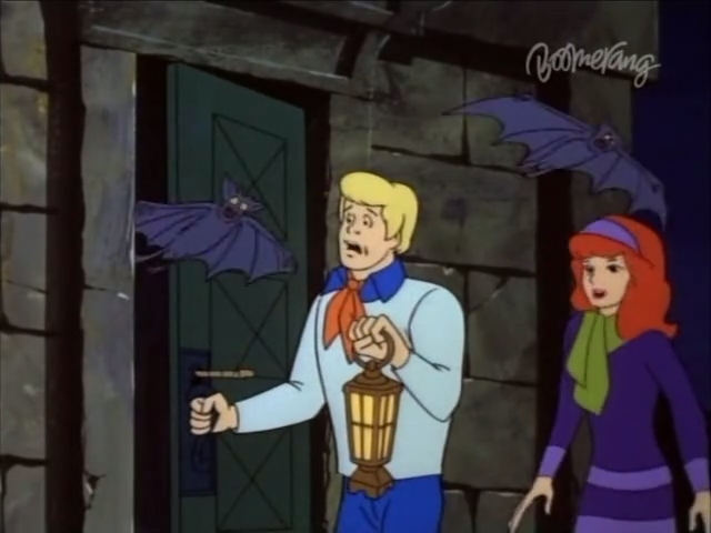 Fred is frightened by a bat at the same moment that he realizes he left the oven on AND at the same time he notices Velma and Fred from the last screenshot looking at him.