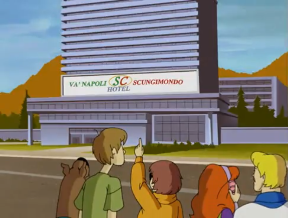 Velma uses a nearby building and her forefinger to teach Shaggy about distance and size perception.