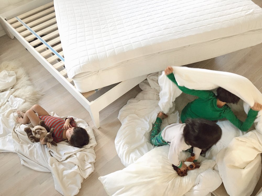 """11:48 a.m. - Trying to change the linens on my bed with 3 kids be like. Have you ever seen a human """"burrito wrapping"""" in action? Yea, turns out my 7-year-old's got mad skills with a giant duvet cover and a hankering for Mexican."""
