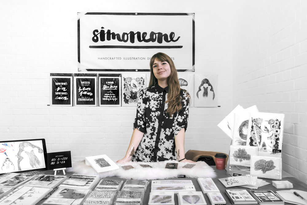 simoneone behind her stand