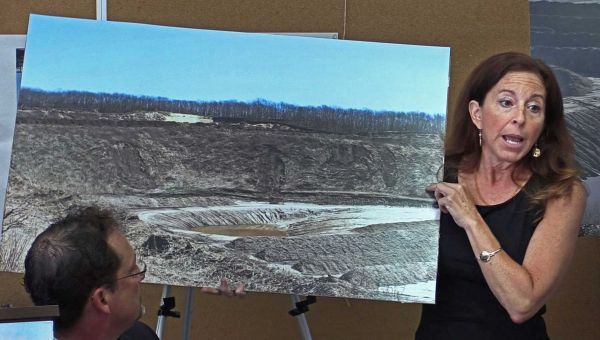 Adrienne Esposito holds a photo of Sand Land Corp. Sand Mine in Noyac during a meeting at the Old Noyac Schoolhouse on Monday, Aug. 18, 2014.  Photo Credit: Chuck Fadely