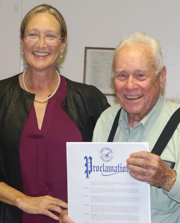 John Anderson receives proclamation from Legislator Bridget Flemming