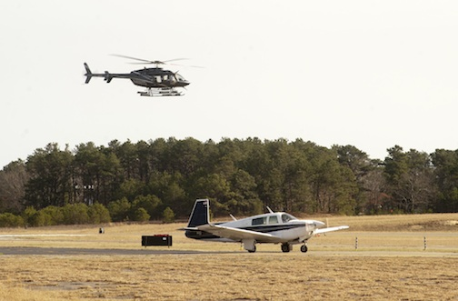 A small private plane taxis on the runway as a helicopter takes off overhead at the East Hampton Airport. Sag Harbor Express