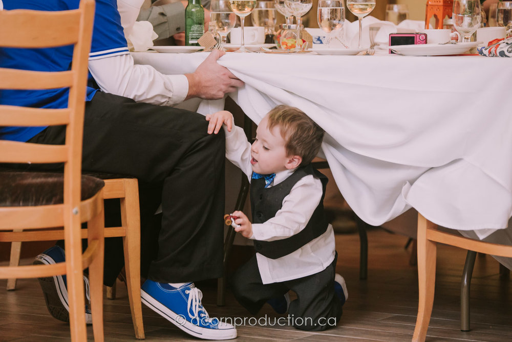 young-boy-playing-under-table-wedding-reception