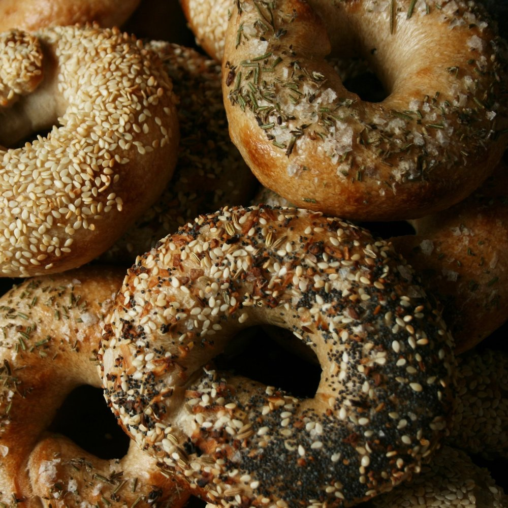 Sourdough Bagels - Our Bagels combine our favorite bagel characteristics. We start with a long fermented sourdough for flavor and texture, then boil our bagels in honey water for a hint of sweetness. The result is chewy, delicious and digestible.  Flavors include plain, sesame, poppy, everything, rosemary/sea salt, and cinnamon/raisin. Slice & Freeze for long-term storage. They also make REALLY good pizza bagelsAdd On to your subscription: 6 for $9 or a Baker's Dozen (13)  for $18