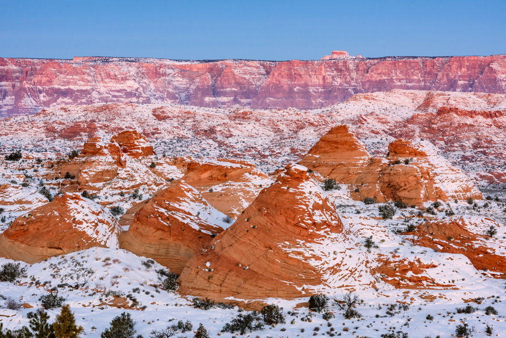 "A New Year's storm blanketed the landscape at the heart of the Colorado Plateau in 2015. Below what is referred to locally as the ""Little Cut"" on the Navajo Nation, the Navajo Sandstone teepees are frosted with the remnants of the storm while snow still clings to the Vermilion Cliffs in the distance."