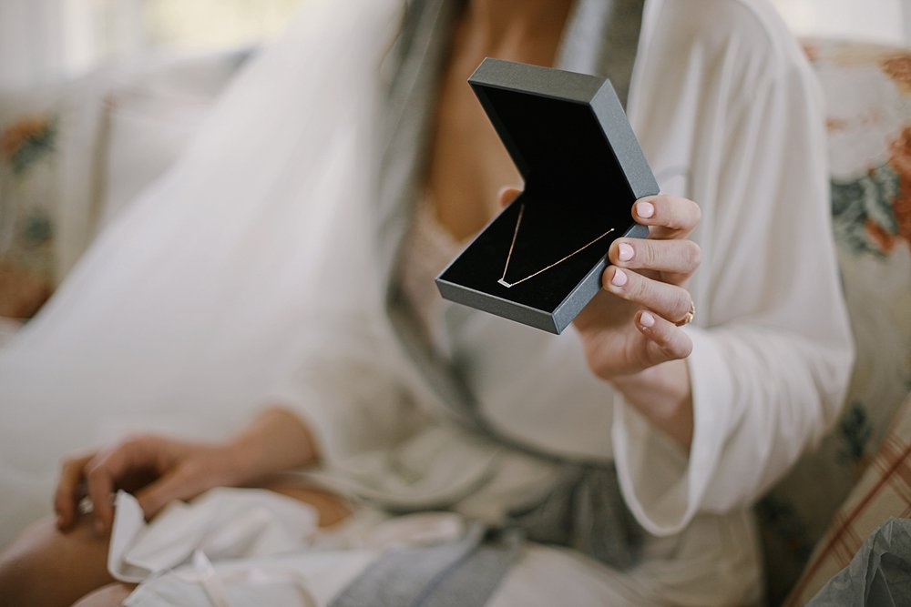 bride opening gift from groom, breckenridge colorado wedding, breckenridge colorado wedding photographer, the church at agape outpost wedding