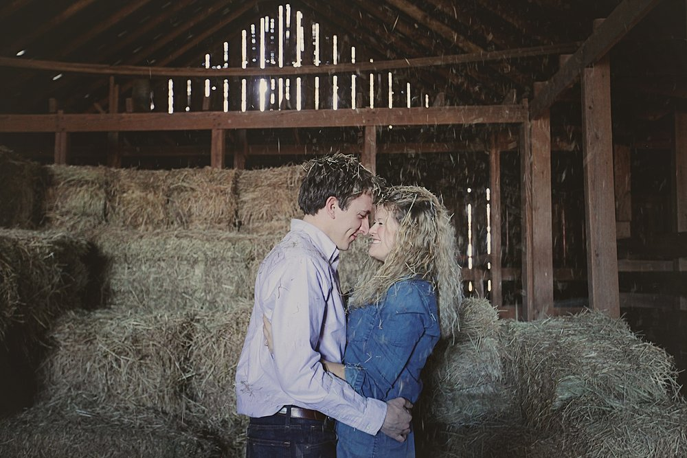 couple posing on haybale, rustic barn engagements, thomas oklahoma wedding photographer, weatherford oklahoma wedding photographer