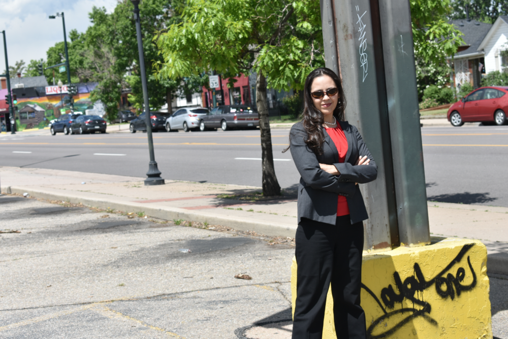 Community Wealth Building Fellow Yessica Holguin stands in the parking lot of a closed Save A Lot in north Denver. Holguin used to frequent the store while living nearby and sees its closure as a sign of the rapidly developing neighborhood. (Credit: Sarah Ford)
