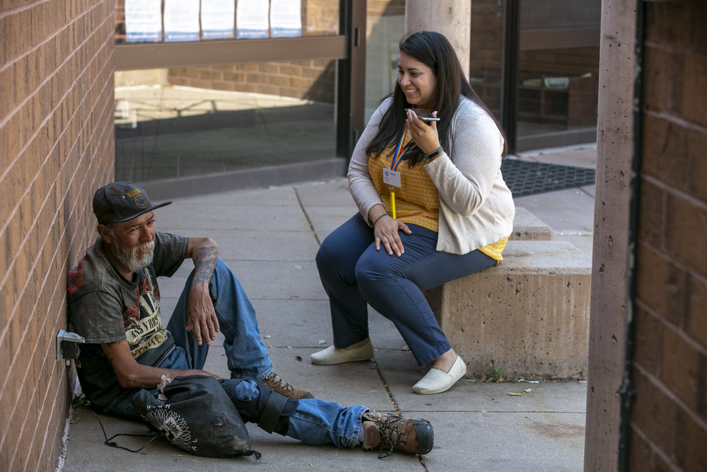 "Sonia Falcon  helps Gabriel schedule a Lyft ride to a medical appointment from the Hampden Branch Library. Lyft partners with Denver resource referral database 2-1-1 to give free rides to medical appointments for those experiencing poverty.  ""Part of my role is assessing what the needs are in the community,"" said Falcon. ""Part of it is about assessing community need working with people experiencing homelessness and making sure they have access to resources. I think another part of the role is working with the staff in the library system making sure they feel secure and prepared to meet the needs as well."""