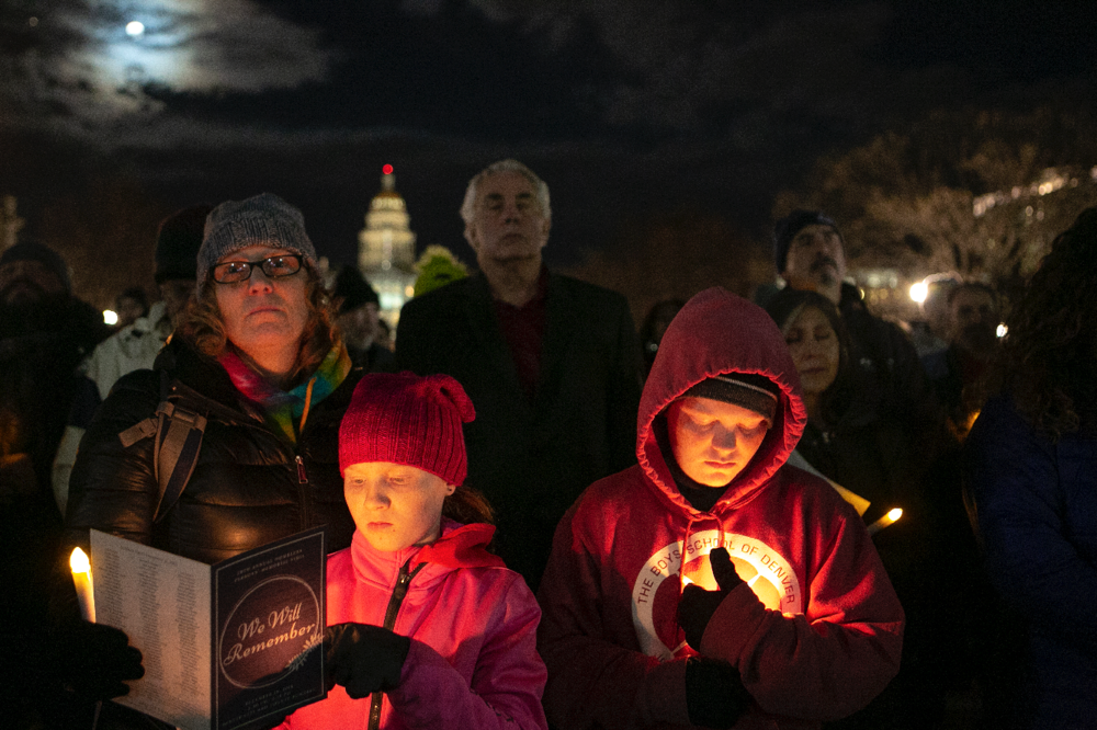 Missy Mishflanagan stands with her children, Sean and Mimi, during the vigil. Mishflanagan works with homeless veterans at the Department of Veteran's Affairs.